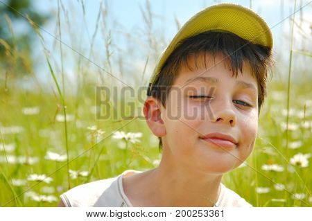 Funny boy sitting in a meadow with daisies and smiling. Dressed in a cap from the sun.
