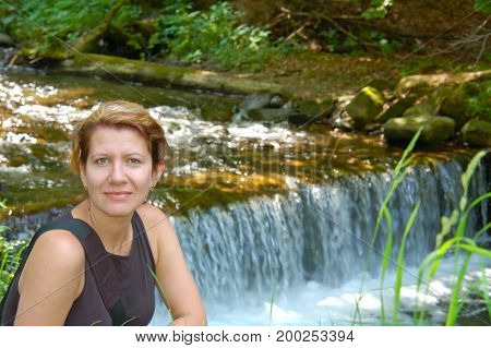 Beautiful woman resting near a small waterfall. Smiling and looking directly into the camera. On the shoulders of her hanging bag for camera