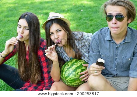 Young man and women eating chocolate ice-cream and watermelon outdoor in summer park. Friends have fun outdoor. Leisure, youth, summertime.