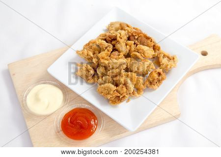 Fried crispy chicken breaded with corn flake crumbs with ketchup on wooden board.