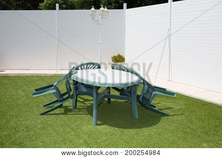 Synthetic Lawn With A Green Plastic Garden Lounge In Garden