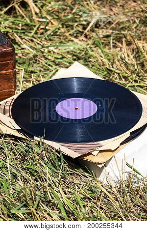 Photo of an Old vinyl record on the grass.