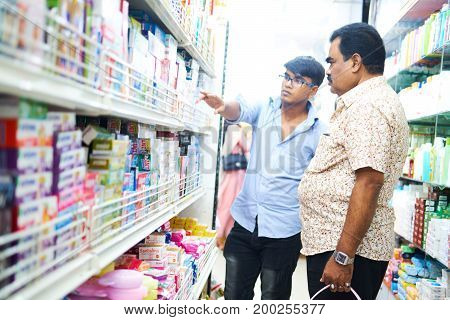 Dhaka, bangladesh, august 2017- a sales man helping a customers to define a product at retail stores located at shavar shopping market in dhaka in bangladesh taken on 17 august 2017.