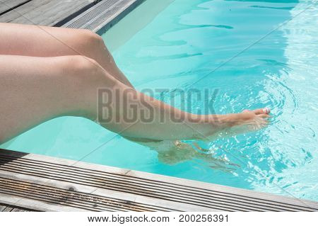 Legs Of Women In Summer In The Blue Swimming Pool