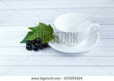 Empty Cup and black currants on wooden background.