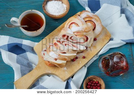 Sweet sliced bun with a cowberry jam on an old cutting board top view