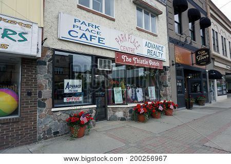CADILLAC, MICHIGAN / UNITED STATES - MAY 31, 2017:  One may drink coffee at the Park Place Café, and buy clothing at the Thistle Patch, on Mitchell Street in Downtown Cadillac.