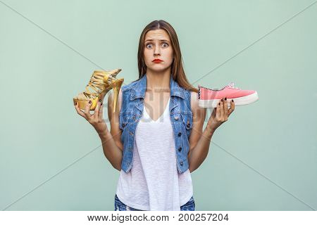 Pretty casual style girl with freckles got choosing sneakers or inconvenient but handsome shoes and thinking. Isolated studio shot on light green background