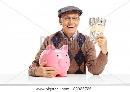 Senior with a piggybank and money bundles sitting at a table isolated on white background