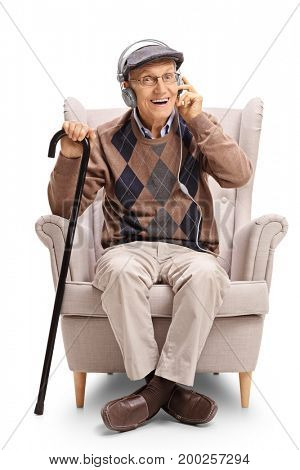 Senior with a pair of headphones and a cane sitting in an armchair isolated on white background