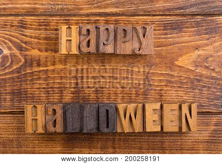 Happy halloween text on a wood background
