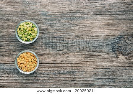 Lentils and green peas in a bowl on wooden surface