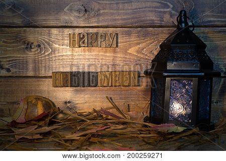 Happy halloween lettering and lantern on a wood background