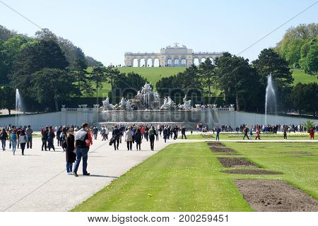 VIENNA, AUSTRIA - APR 30th, 2017: Neptune Fountain Neptunbrunnen in great parterre of Schoenbrunn public park with flowers in the foreground and Gloriette in the back, Schoenbrunn palace - former imperial summer residence, built and remodelled during reig