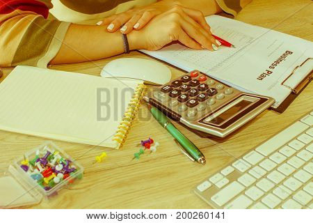 Female with Business plan calculator and pen on the table. Young woman working in office sitting at desk using computer - Retro color