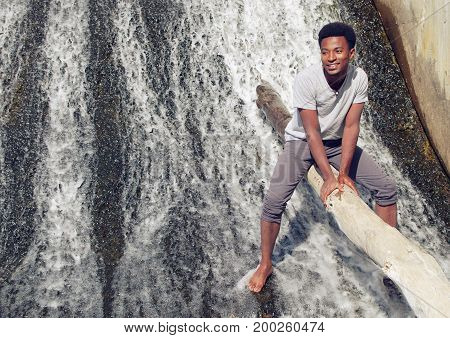 man in river sitting on tree trunk water fall vacation sun light