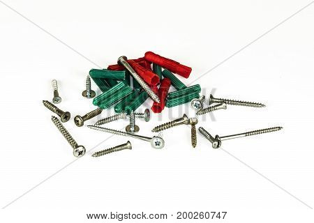 Self-tapping screws and plastic dowels on a light background