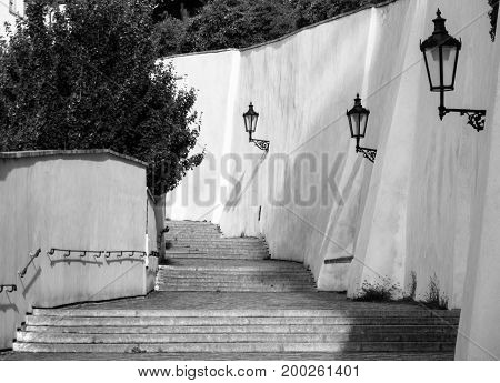 Old Castle Stairs on Prague Castle. Medieval stairway with vintage lamps, Prague, Czech Republic. Black and white image