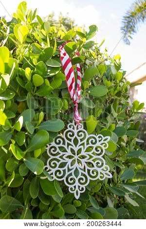 holiday snowflake decoration hung from a hedge