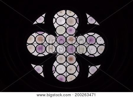 round purple stained glass window with cross or flower design