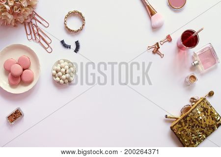 Modern styled desk top with fashion and beauty items with rose gold accents. Food and drink. Copy space.