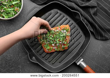 Woman sprinkling salmon fillet with herbs in grill frying pan