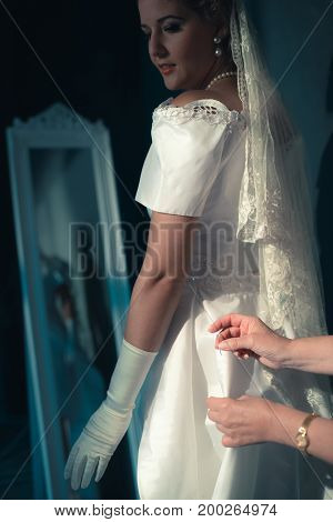 Vintage 1940S Bride Looking Over Shoulder At Seamstress Finishing Dress.