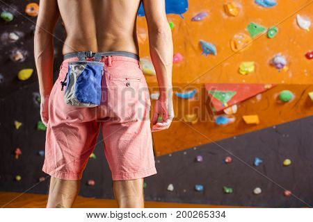 Young male rock climber in indoor climbing gym cropped view