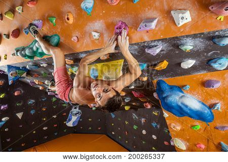 Young man bouldering in indoor climbing gym and looking at camera