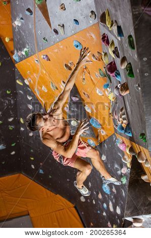 Young man climbing with top rope in indoor climbing gym falling down while being belayed