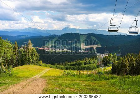 summer view of Carpathian Mountains landscape in Bukovel, Ukraine. Green forests, hills, grassy meadows and blue sky.