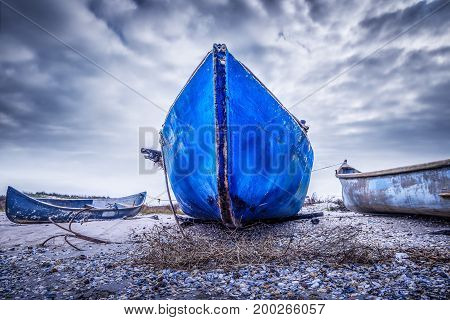 blue old fishing boat on the beach