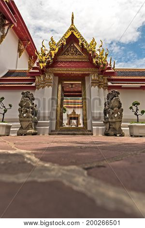 Low down angle of an impressive doorway at Wat Pho Buddhist temple Bangkok Thailand.