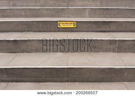 Paved grey public steps with a yellow