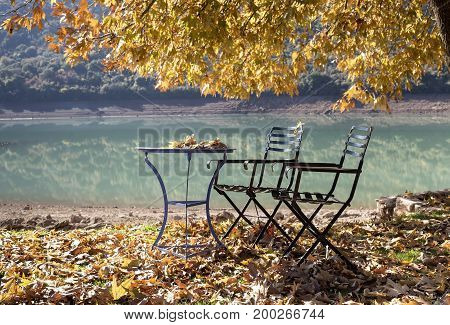 Table and chairs on the background of a mountain lake in the fall
