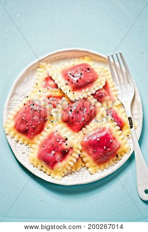 Beetroot ravioli with olive oil on blue background