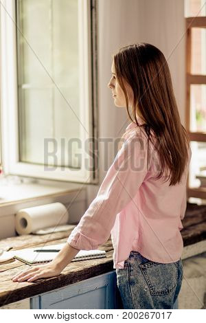 Rear view of young girl standing close to window and wooden desk. Female thinking and looking through open window.