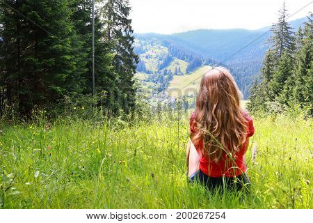Young brown-haired woman female with curly hair sitting at green grass glade at mountain landscape background in sunny summer day. Carpathian Mountains, wild mountain landscape Ukraine, Vorohta