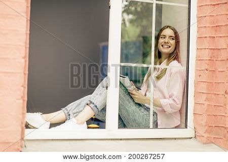 Female sitting on window sill, dreaming looking aside. Girl sitting close to open window with notebook on her knees.