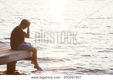 Young man with hand on head and looking over water