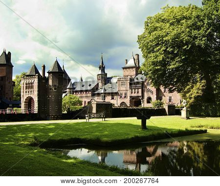 Medieval Castle De Haar from side of Back Yard with Reflection on Pond against Cloudy Sky Outdoors. Utrecht Netherlands