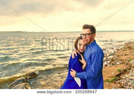 Young beautiful couple outdoor fashion portrait. Attractive boy and girl posing and kissing on a beach in sunny cold weather.