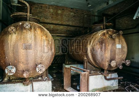 Large rusty iron barrels in an abandoned factory. Abandoned industrial concept