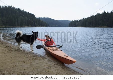 Young woman caress Alaskan Malamute sitting in her kayak