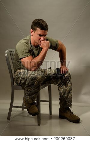 The army man sits and thinks about battle.