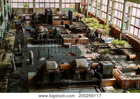 Abandoned factory overgrown with plants, industrial background