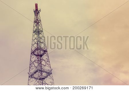 Cellular tower on a cloudy sky background, toned, copy space