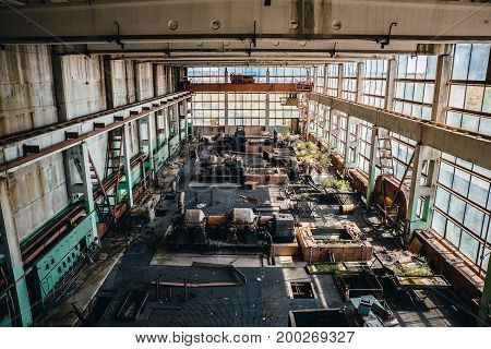 Abandoned industrial interior, large workshop with big windows and rusty iron metal machines or tools, toned