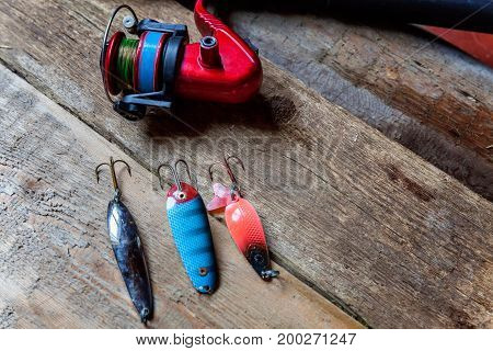 Fishing tools and accessories on a wooden surface and place for text