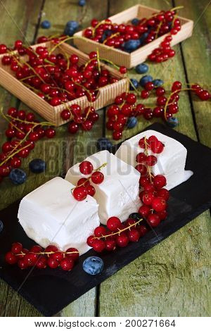 Ice cream with red currant berries. Creamy ice cream and boxes with red currants on an old wooden table.